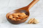 Shelled almonds in a wooden spoon on a light background — Stock Photo