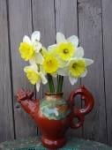 Daffodils in a vase on a wooden background — Stock Photo