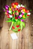 Bright tulips in glass vase — Stock Photo