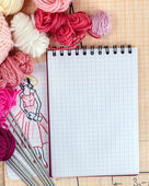 Open notepad on tracing paper background, surrounded by balls of wool and needles — Stockfoto