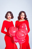 Two young beautiful women in a long red dress with balloons — 图库照片