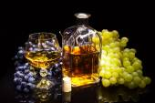 Bottle with a glass of brandy and grapes — Stock Photo