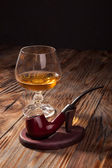 Glass of brandy and a pipe  — Stock Photo