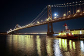 Oakland Bay Bridge and pusher boat in San Francisco at night — Stock Photo