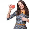 Beautiful woman in colorfull dress holding empty credit card and pointing at it,  isolated on white background — Stock Photo #69177625