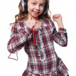 Pretty little girl singing in imaginary microphone with headphones on his head isolated over white background — Stock Photo #69426397