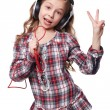 Pretty little girl singing in imaginary microphone with headphones on his head isolated over white background — Stock Photo #69426447