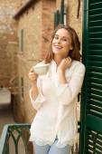 Portrait of happy young woman with cup of hot beverage — Stock Photo