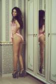 Photo of young  girl in erotic lingerie posing in the interior — Stock Photo