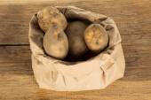 Unwashed potatoes in a paper bag islated on white — Stock Photo
