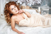 Beautiful brunette young woman in luxurious long dress in expensive interior — Stock Photo