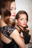Portarit of beautiful twins young women in gorgeous evening dresses — Stock Photo