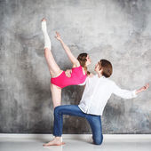 Young beautiful couple of dancers posing on studio background — Stock Photo