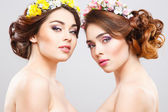 Portrait of beautiful twins young women with perfect make-up and hair-style with flowers in hair — Stock Photo