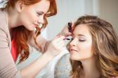 Makeup artist preparing bride before the wedding in a morning — Stock Photo