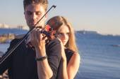 Beautiful couple violinist and young woman together near sea bay — Stock Photo