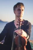 Handsome young man violinist over picturesque background — Stock Photo