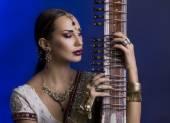 Beautiful Indian Woman in Sari with Oriental Jewelry Playing the — Stock Photo