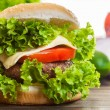 Cheeseburger with lettuce, onions and tomato in a sesame bun — Stock Photo #52350909