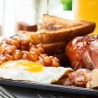 Full English breakfast with bacon, sausage, egg, baked beans and orange juice — Stock Photo #52351283