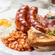 Full English breakfast with bacon, sausage, fried egg and baked beans — 图库照片