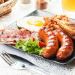 Full English breakfast with bacon, sausage, egg, baked beans and orange juice — Stock Photo #52746295