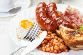 Full English breakfast with bacon, sausage, fried egg and baked  — Stock Photo