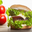 Cheeseburger with lettuce, onions and tomato in a sesame bun — Stock Photo #52765785