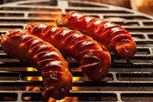 Grilling sausages on barbecue grill — Stock Photo