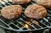 Raw burgers on barbecue grill with fire — Stock Photo