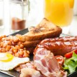 Full English breakfast with bacon, sausage, egg, baked beans and orange juice — Stock Photo #53750209