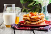 Pancakes with honey, fruit and glass of milk — Foto Stock