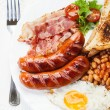 Full English breakfast with bacon, sausage, fried egg and baked beans — Stock fotografie #54164801