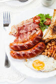 Full English breakfast with bacon, sausage, fried egg and baked beans — Foto Stock