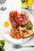 Full English breakfast with bacon, sausage, fried egg and baked  — Foto Stock