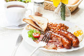 Full English breakfast with bacon, sausage, fried egg and baked  — Foto de Stock