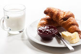 Fresh croissants with butter and a glass of milk — Stock Photo