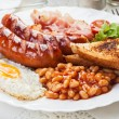 Full English breakfast with bacon, sausage, fried egg and baked beans — Stock fotografie #54735439