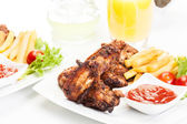 Chicken wings with fries french and spicy sauce — Stock Photo