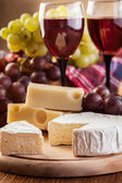Cheese with a bottle and glasses of red wine — Stock Photo