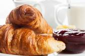 Croissants with butter and a glass of milk on a plate — Stock Photo