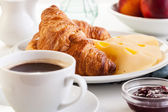 Croissants with cheese, fruits and coffee — Stock Photo