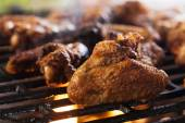 Grilling chicken wings on barbecue grill — Stock Photo