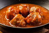 Meatballs with tomato sauce on black pan — Foto Stock