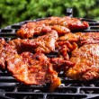 Grilling pork steaks on barbecue grill — Stock Photo #65490777