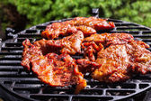 Grilling pork steaks on barbecue grill — Stock Photo