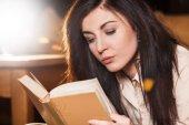 Kobieta leżąc na jej kanapie czytając książkę w domu — Zdjęcie stockowe
