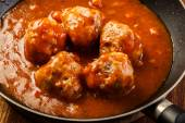 Meatballs with tomato sauce on black pan — Stock Photo