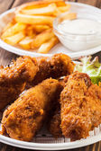 Crisp crunchy chicken wings with chips — Stock Photo