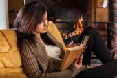 Woman reading a book by fireplace — Stock Photo